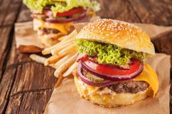 Fresh hamburger with fries served on wood Royalty Free Stock Images