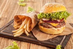 Fresh hamburger with fries served on wood Stock Photos