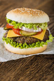 Fresh hamburger. Vertical shoot of the classic hamburger with cheese and vegetables on the baking paper and wooden tabletop Stock Photography