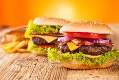 Fresh hamburgers on wooden planks Royalty Free Stock Photos