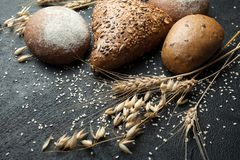 Fresh hand made bread, ear and grain on a black background royalty free stock photos