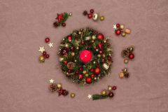 Fresh handmade Christmas wreath decorated with red and gold Christmas decorations, fir-cones and walnuts with a burning red candle Royalty Free Stock Photography