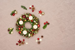 Fresh handmade Christmas wreath decorated with red and gold Christmas decorations, fir-cones and walnuts with four gold burning ca Royalty Free Stock Photography
