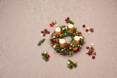 Fresh handmade Christmas wreath decorated with red and gold Christmas decorations, fir-cones and walnuts with gold candles Royalty Free Stock Photo