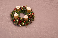 Fresh handmade Christmas wreath decorated with red and gold Christmas decorations, fir-cones and walnuts with gold candles Royalty Free Stock Photos