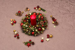 Fresh handmade Christmas wreath decorated with red and gold Christmas decorations, fir-cones and walnuts with a red burning candle Royalty Free Stock Photography