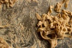 Fresh handmade pasta. Fresh wholegrain handmade tagliatelle in italy, with grey background Royalty Free Stock Photos