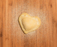 Fresh,handmade,single raviolo in the shape of heart,covered with flour and  placed on the wooden table and covered with flour. Royalty Free Stock Photography