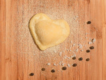 Fresh,handmade single raviolo in the shape of heart with few grains of black pepper and coarse salt. Royalty Free Stock Photo