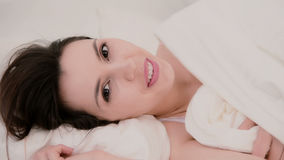 Fresh and happy brunette woman in bed at home. Beautiful girl hides under a blanket and smiling. Stock Photography