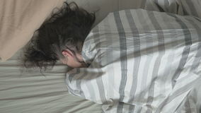 Fresh and happy woman in bed wakes up in the morning, opening his eyes and smiles, then falls back asleep. The view from stock video