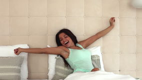 Fresh and happy woman in bed wakes up in the morning stock footage