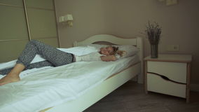 Fresh and happy woman in bed wakes up in the morning smiling stock video