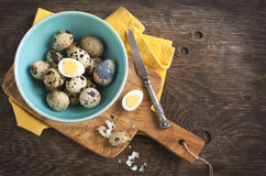 Fresh hard boiled quail eggs with shell beside on cooking board Stock Photo
