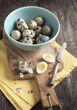 Fresh hard boiled quail eggs with shell beside on cooking board Stock Image