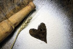 Fresh harvested wheat grain on wheat flour background. Baking concept on wood background, sprinkled flour with heart.