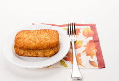 Fresh hash brown. Delicious breakfast with fresh hash brown on white dish, decorative napkin, and fork royalty free stock photos