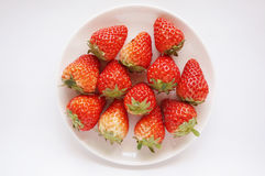 Fresh havested group of red strawberries on plate. Close up of photo of very fresh harvested red strawberries on white plate  on white background Stock Image