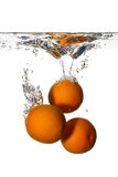 Fresh and Health Oranges Falling into Clean Water Isolated on White Background. royalty free stock photography
