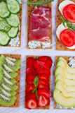 Fresh healthy appetizer snack with crispbread, fruits, berries, hamon and cheese. Royalty Free Stock Photos