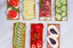 Fresh healthy appetizer snack with crispbread, fruits, berries, hamon and cheese. Stock Image