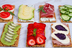 Fresh healthy appetizer snack with crispbread, fruits, berries, hamon and cheese. Stock Images