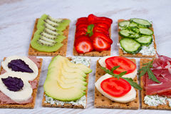 Fresh healthy appetizer snack with crispbread, fruits, berries, hamon and cheese. Stock Photos