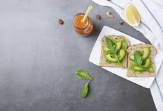 Fresh healthy avocado sandwich in plate with orange juice on table background with free text space for diet menu.  royalty free stock photos