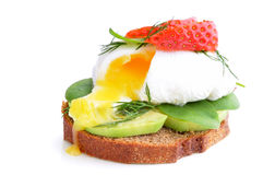Fresh Healthy Breakfast:Poached egg on piece of rye bread with Avocado slices,Spinach and Strawberry . Stock Images
