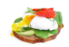 Fresh Healthy Breakfast:Poached egg on piece of rye bread with Avocado slices,Spinach and Strawberry . Royalty Free Stock Images