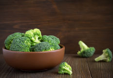 Fresh healthy broccoli in bowl on wooden table. Stock Photos