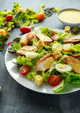 Fresh healthy Caesar salad with chicken, egg quail, tomatoes, Cheese and Croutons in a white plate Royalty Free Stock Image