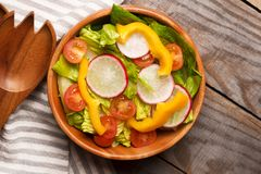 Fresh healthy close up salad with lettuce,tomatoes,pepper,radish. Fresh healthy close up salad with cos lettuce, cherry tomatoes, bell pepper, radish on  wooden Stock Photo