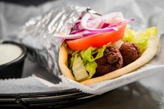Falafel in a Pita Pocket. Fresh and healthy falafel with tzatziki tomato red onion and iceberg lettuce in pita bread royalty free stock image