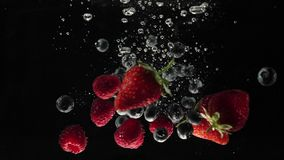 Fresh healthy food. Strawberries, raspberries and blueberries falling into water on black background. Fresh fruits splashing.