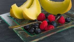 Fresh healthy fruit on a glass dessert plate on black background. Healthy eating concept Royalty Free Stock Photos