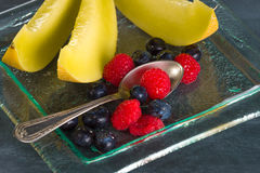 Fresh healthy fruit on a glass dessert plate on black background. Healthy eating concept Royalty Free Stock Photo