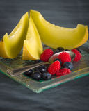 Fresh healthy fruit on a glass dessert plate on black background. Healthy eating concept Royalty Free Stock Images