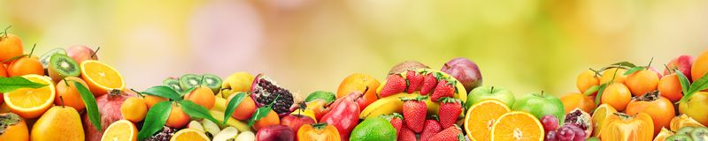 Fresh healthy fruits on natural blurred multicolored background. Free space for text Royalty Free Stock Images