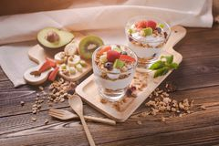 A fresh healthy garnola with yogurt and mix fruits in glasses on stock photos