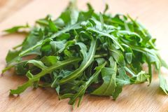 Fresh healthy green arugula leaves on light wooden background.  royalty free stock images