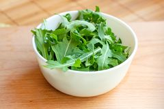 Fresh healthy green arugula leaves in a white bowl on light wooden background.  royalty free stock photos