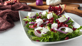 Fresh healthy green salad with pomegranate seeds, onion and feta cheese Stock Photos