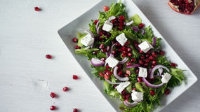 Fresh healthy green salad with pomegranate seeds, onion and feta cheese. Top view Royalty Free Stock Photos