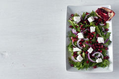Fresh healthy green salad with pomegranate seeds, onion and feta cheese. Top view, copy space Stock Image