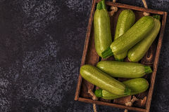 Fresh healthy green zucchini courgettes in brown wooden box. Fresh healthy green zucchini courgettes in brown wooden box, top view Stock Photos