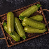 Fresh healthy green zucchini courgettes in brown wooden box. Fresh healthy green zucchini courgettes in brown wooden box, top view Royalty Free Stock Image