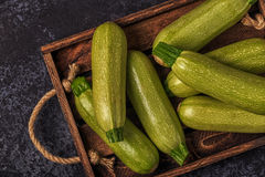 Fresh healthy green zucchini courgettes in brown wooden box. Fresh healthy green zucchini courgettes in brown wooden box, top view Royalty Free Stock Photo