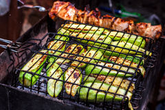 Fresh healthy green zucchini courgettes cucumber preparing on a barbecue grill over charcoal. Royalty Free Stock Photos