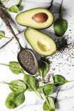 Fresh healthy ingredients for a breakfast on a marble table. Healthy life concept with avocado,chia seeds and spinach. Leaves royalty free stock photo